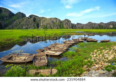 Landscape with boat, mountains and clouds in Van Long Natural reserve of Ninh Binh, Vietnam  - stock photo