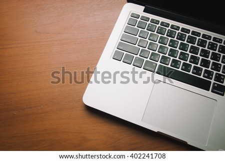 Laptop with isolated screen on old wooden background.Vintage style photo with custom white balance, color filters, soft focus effect, and some fine film grain added - stock photo
