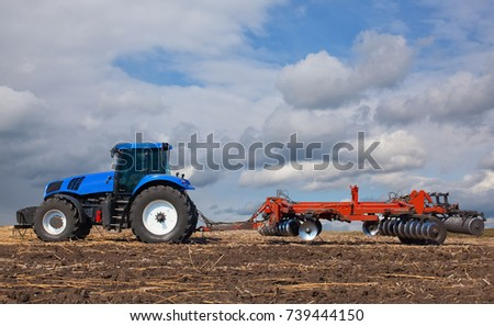 large blue tractor, plowing field against the beautiful sky. Work of agricultural machinery. Harvest