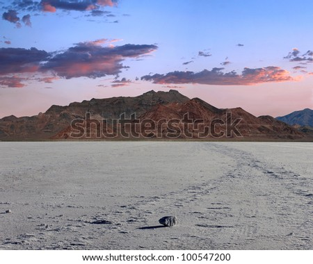 Large chunk of salt casting a long shadow. mountains in center frame with a beautiful blue to pink sky and clouds./ Bonneville Salt Flats Large Chunk and Sunset./ Desert beauty and hot rodder heaven. - stock photo