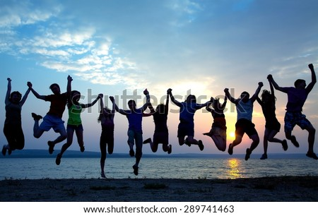 large group of young people having fun and jumping on the beach at sunset