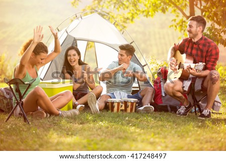 Laughing group of young people enjoy in music of drums and guitar on camping trip