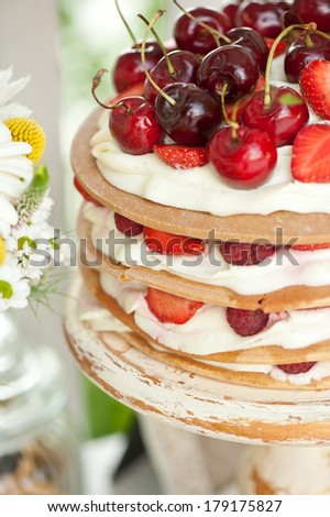 Layer cakes with protein cream and fresh cherry and berries on a cake stand outdoors