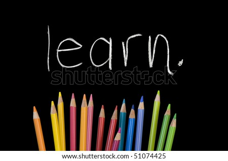 """learn"" written on chalkboard with rainbow colored pencil crayons"