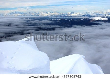LECCO, ITALY - CIRCA FEBRUARY 2016: a panoramic view from the top of Mount Southern Grigna:  snowy ridge, a layer of clouds and in the background the Alps.