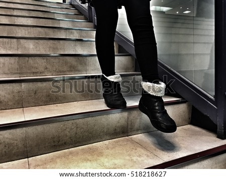 leg of girl  wearing  black boots. walking down stairs style dramatic