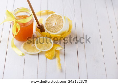 Lemons and honey in glass jar on white  wooden background in rustic style . Selective focus. - stock photo