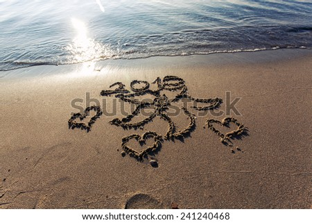 2015 lettering, hearts and flower drawings on sand at beach. we will be in love in 2015 - stock photo