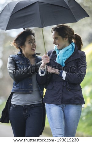 Lifestyle image of Caucasian and Asian women walking under an umbrella. Two happy female friends out having fun together. - stock photo