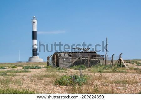 lighthouse with derelict wooden building in kent - stock photo