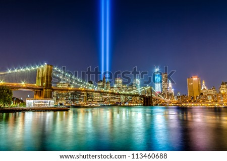 911 Lights over NYC - September eleventh memorial beams from over Brooklyn Bridge in Manhattan across the East River at night - stock photo