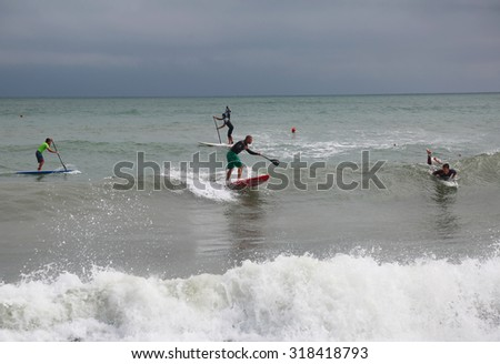 LIGNANO - AUGUST 24: surfers at Adriatic sea on August 24, 2015 in Lignano, Italy. This coast is popular among hobby and professional surfer in summer.