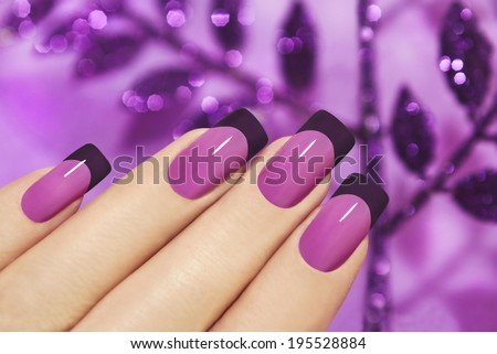 Lilac manicure on female hand with purple sparkles. - stock photo