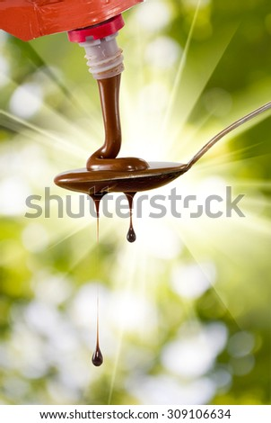 liquid chocolate on a spoon on a green background - stock photo