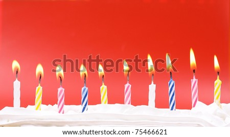 10 lit birthday candles in bright colors with red background - stock photo