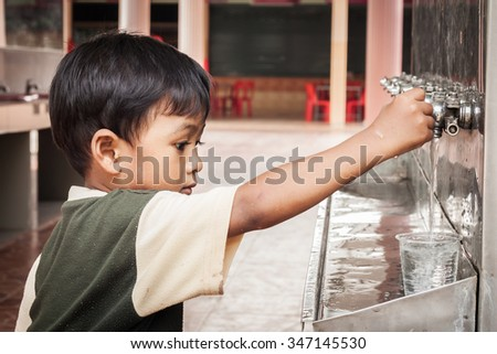 little asian boy press the drinking water - stock photo