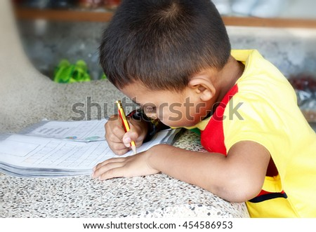 Little asian boy use pencil writing on notebook for writing book with intently.