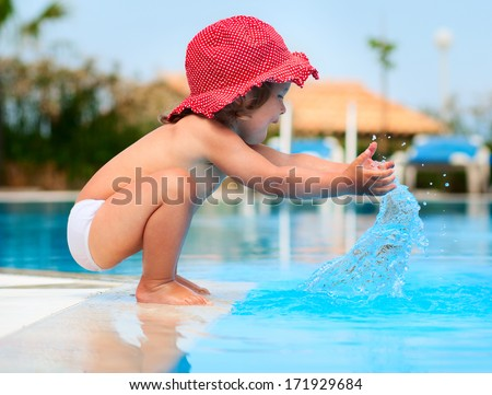 Little baby have a fun with a splash near swimming pool - stock photo