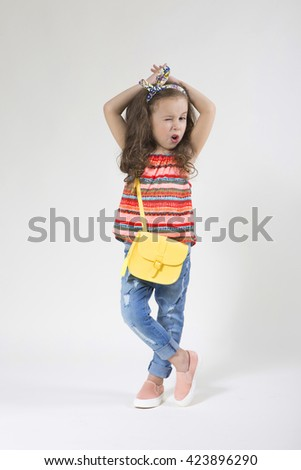 Little beautiful smiling girl in jeans and a bright summer clothes posing positively on a light background in studio