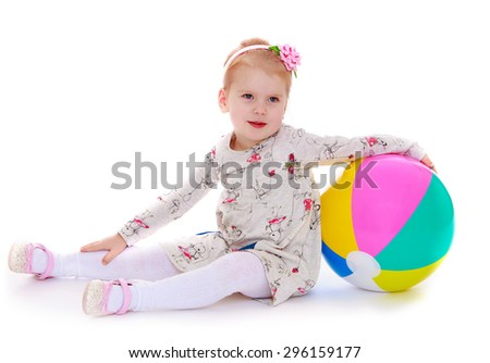 little blonde girl with bow on her head in a white dress sitting on the floor holding the arm of a big bouncy ball