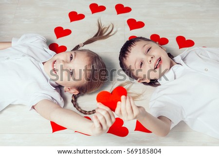 Little Boy And Girl Lying On The Floor. Concept Of Happy Valentine Day And  Brother
