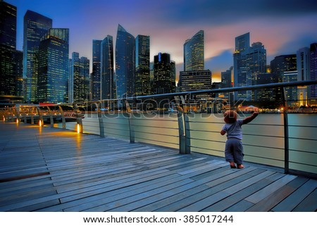 Little boy in a big city at sunset - stock photo
