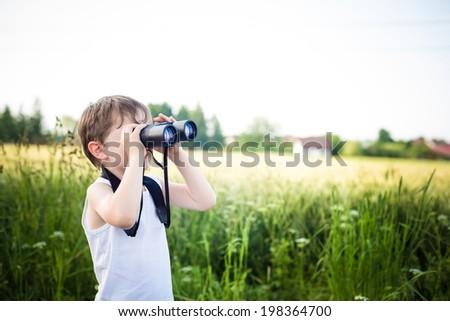 little boy in a field looking through binoculars - sunny day - stock photo