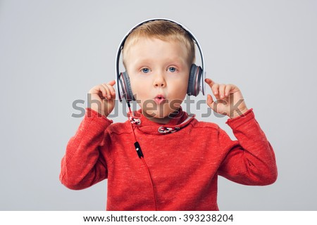 Little boy in red pullover enjoying his music on headphones (isolated on grey) Studio shot of boy with headphones - stock photo