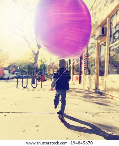 little boy running with a balloon done with a retro vintage instagram filter  - stock photo