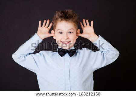 Little boy with funny face on black background