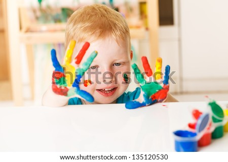 little boy with hands painted in colorful paints ready for hand prints - stock photo