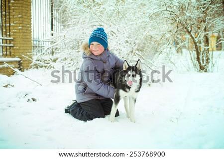 Little boy with Husky dog on the snow - stock photo