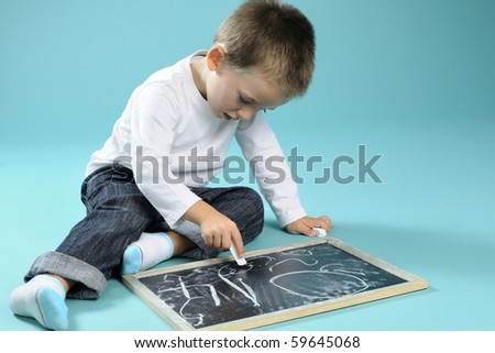 little boy writing on blackboard