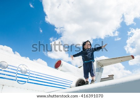 Little child boy plays pilot standing on aircraft wing. Child on the background of blue sky and white clouds. Childplays and dreams of becoming a pilot. - stock photo