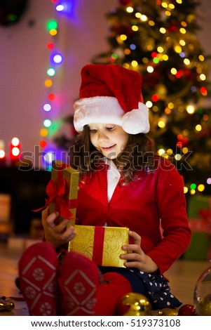 little girl are opening presents around the Christmas tree