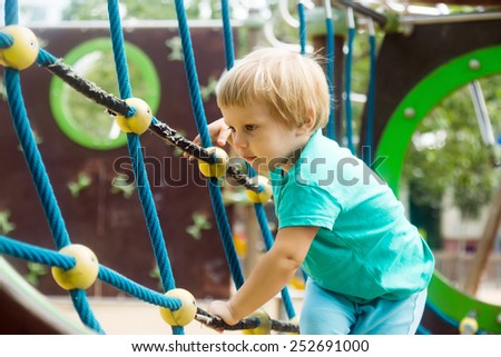 little girl climbing the ropes of challenge net at playground  - stock photo