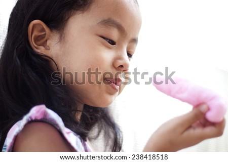 little girl eating candy floss - stock photo