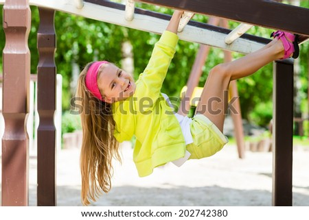 little girl enjoys playing in a children playground, Outdoor portrait - stock photo