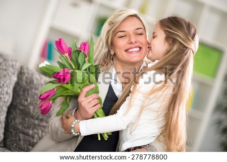 Little girl  giving flowers to his mom on mother's day - stock photo