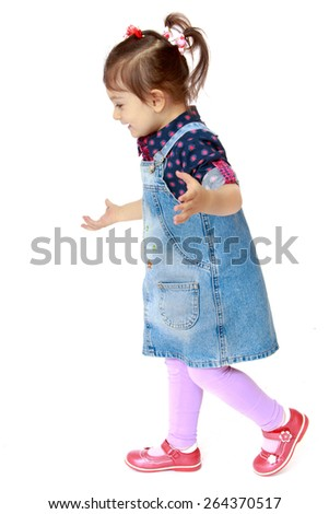 Little girl in a denim dress on white background - isolated on white background