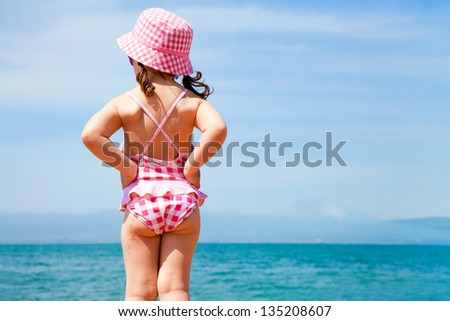 little girl in a swimming suit looks at the sea