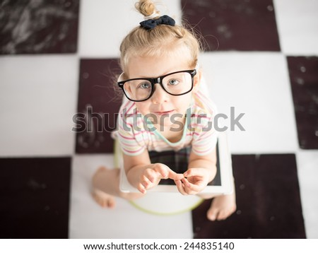 Little girl on a potty with tablet PC - stock photo