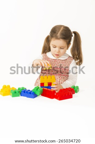 Little girl playing with construction blocks, studio shot on white background - stock photo