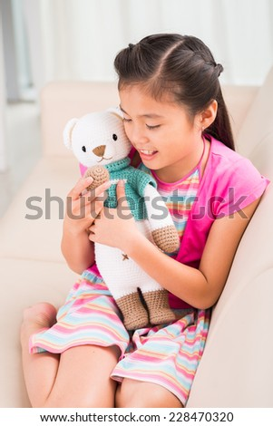 Little girl playing with her favorite knitted toy sitting on sofa