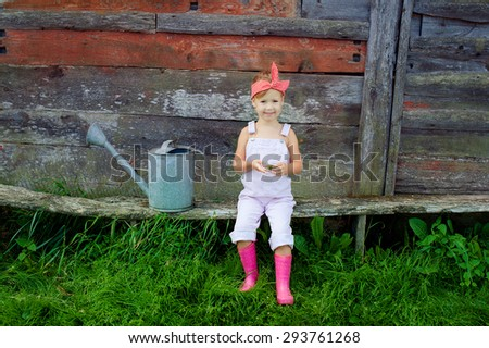 little girl sitting on a bench in the garden - stock photo