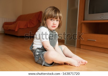 little girl sitting on the floor and sad - stock photo