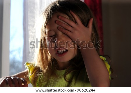 Little girl  upset and crying near the window