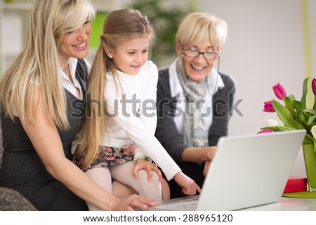 Little girl using laptop with mother and grandmother, modern technology for all generations - stock photo