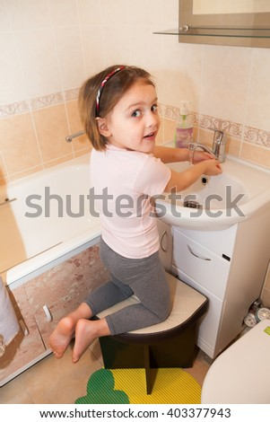 little girl washing her hands with soap by   sink in   bathroom.