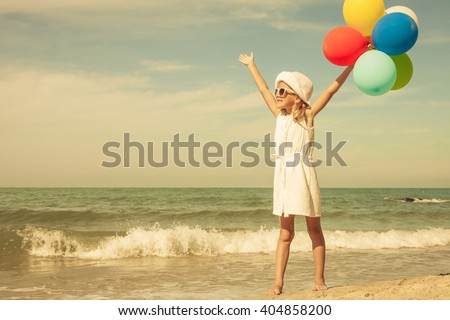 Little girl with balloons  standing on the beach at the day time. Concept of friendly family. - stock photo